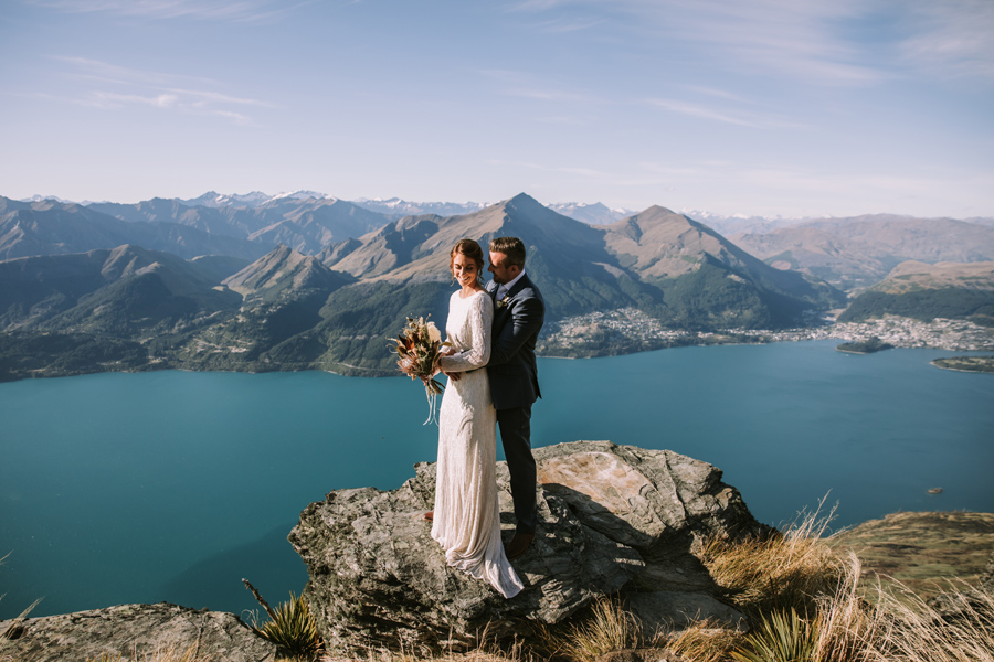 A bride and groom embrace on a mountain top, on their Queenstown wedding day. The lake behind them is blue, and the mountains in the distance stretch as far as the horizon. With photography by Alpine Image Company.