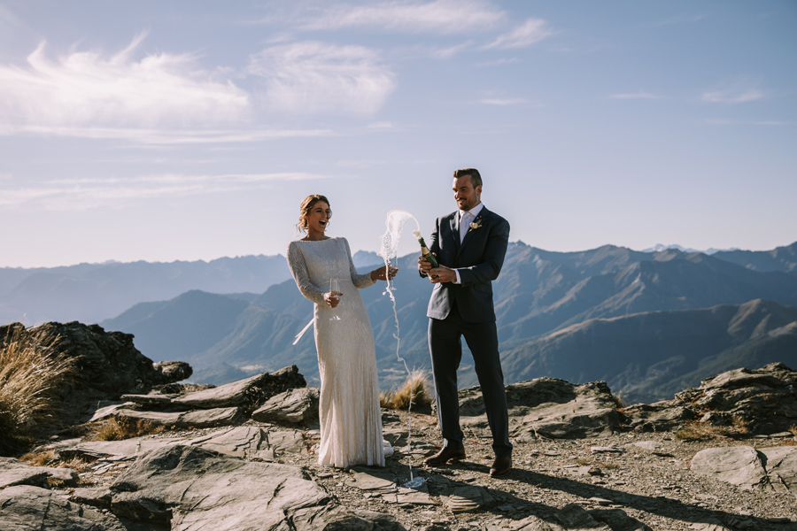 A bride and groom cheer and pop a bottle of bubbles on their wedding day. They are standing on Cecil Peak Ledge. The sky is blue, and there are mountains behind them. With photography by Alpine Image Company.