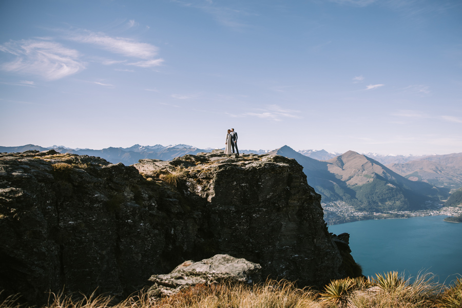 A bride and groom share a kiss on their Queenstown wedding day. They are standing on a huge rocky outcrop, with a lake and mountains in the distance. With photography by Alpine Image Company.