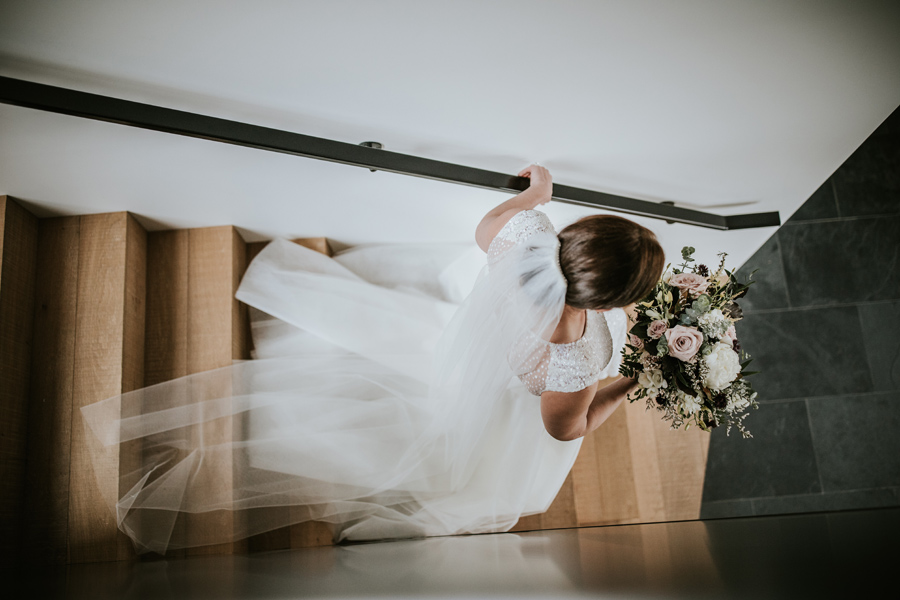A bride walks down the stairs on the way to her way to her wedding ceremony. With photography by Alpine Image Company.