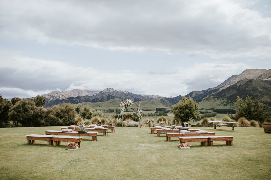 A ceremony set up without any guests in yet. It overlooks onto mountains, with a beautiful floral archway as the centrepeice. With photography by Alpine Image Company.