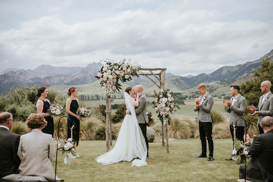 A bride and groom share a kiss on their wedding day, at the end of the ceremony. They stand in front of a wooden floral arch, with mountains and fields in the background. With photography by Alpine Image Company.