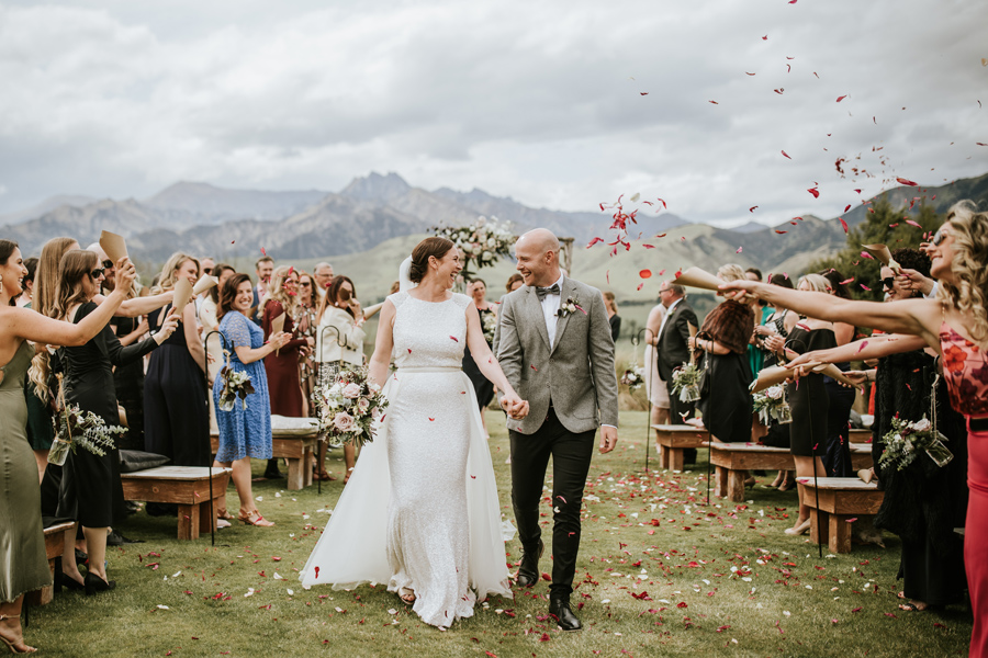 A bride and groom hold hands and walk down the aisle. They are smiling and laughing with each other. Their guests throw petals over them. There are mountains in the background. With photography by Alpine Image Company.