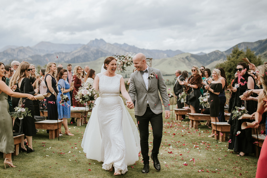 A bride and groom beam with happiness as they walk down the aisle on their wedding day. There are mountains and happy guests clapping in the background. With photography by Alpine Image Company.