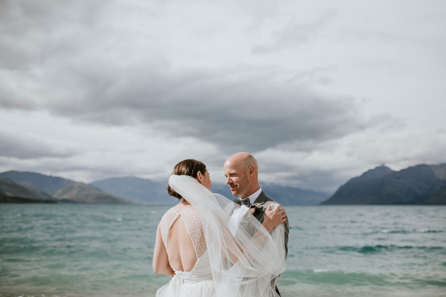 A bride and groom embrace infront of a beautiful blue lake, on their wedding day. The bride holds her veil around the groom, and he smiles at her. There is a big lake, and mountains in the backgrounsd. With photography by Alpine Image Company.