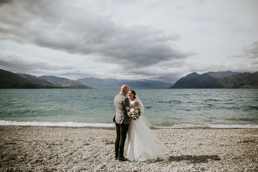 A bride and groom look into each others eyes and stand in front of a blue lake on their wedding day. There are mountains in the background. With photography by Alpine Image Company.