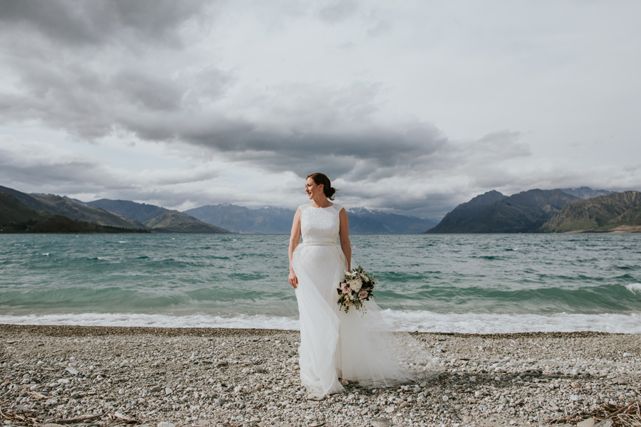 A bride stands gracefully in front of Lake Hawea, on her Wanaka Wedding Day. The sun hits her face, as she looks off to the distance. The lake is pure blue, and the mountains rise up in the background. With photography by Alpine Image Company.