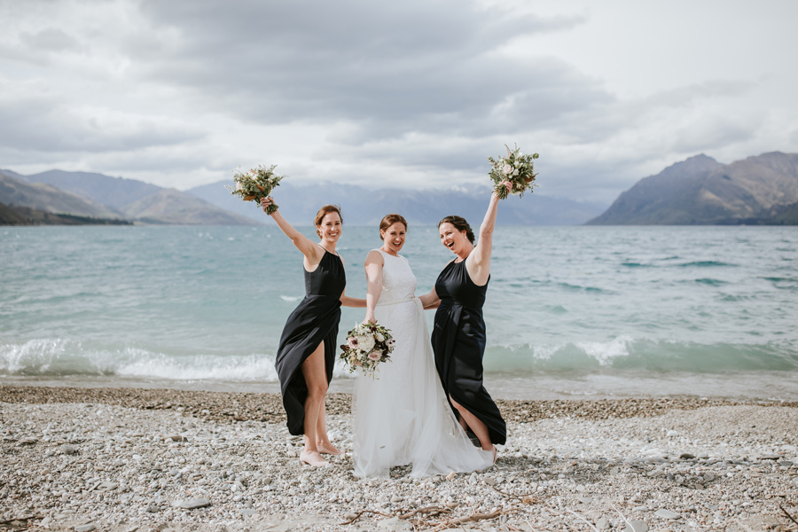 A bride and her bridesmaids happily raise their boquets in the air, celebrating the bride's wanaka wedding. They stand in front of Lake Hawea, with mountains in the distance. With photography by Alpine Image Company.