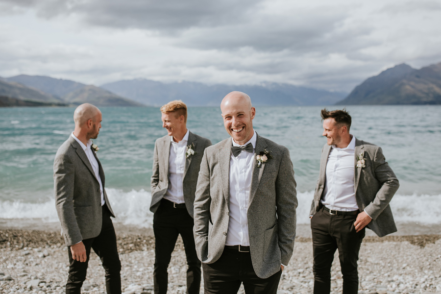 A groom smiles at the camera, as his groomsmen laugh together behind him, on a wanaka wedding day. They are standing in front of a large, blue lake. There are mountains in the distance and clouds in the sky. With photography by Alpine Image Company.