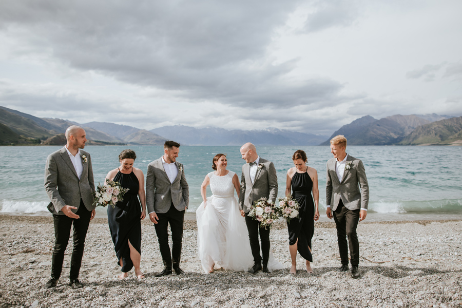 A bridal party walk and laugh together, on a wanaka wedding day. There are mountains and a large blue lake in the background. With photography by Alpine Image Company.