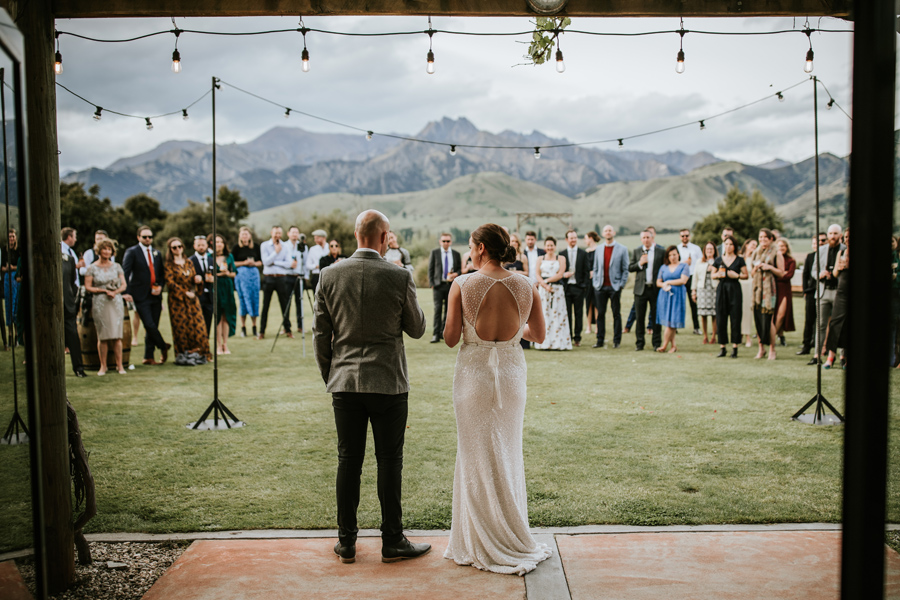 A group of guests look on, as a bride and groom face them with their backs to the viewer, at their wedding reception, as they give a speech. There are clouds in the sky, and mountains in the background. With photography by Alpine Image Company.