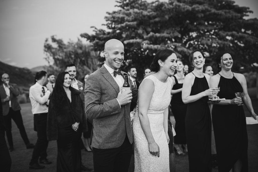 A bride and groom laugh at the speeches they are listening to. They are standing outside, with their wedding guests. It is a warm summers evening. With photography by Alpine Image Company.