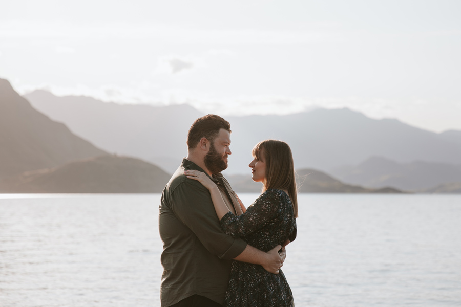 A couple cuddle up next to lake Wanaka with the mountains behind them and a warm glow of sunshine. Photography by Alpine Image Company.