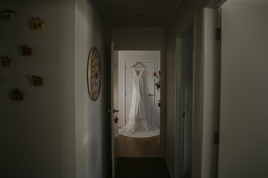 A beautiful white lace wedding dress hangs at the end of a long hallway, there are flowers poking around the corner. Photography by Alpine Image Company.