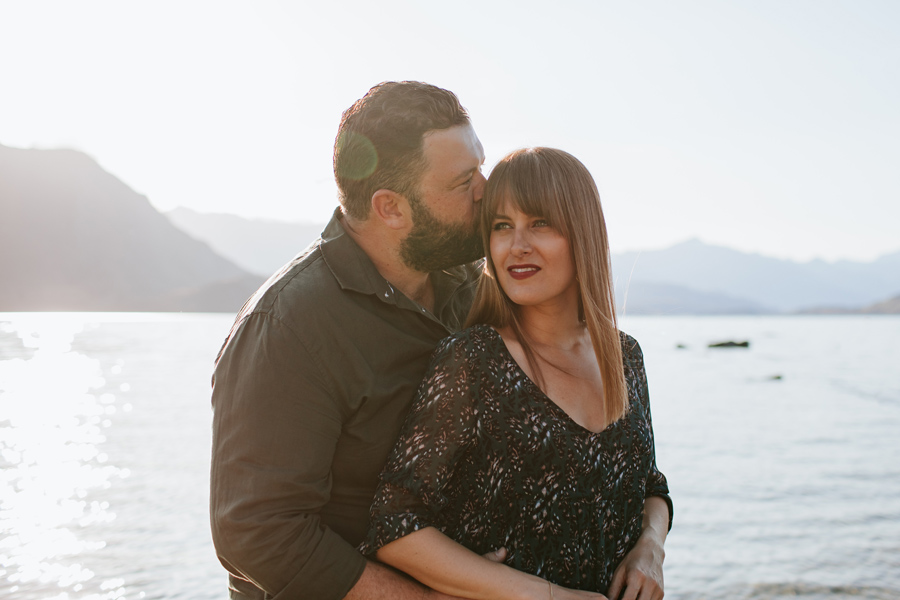 A man kisses a woman on the head with a sun flare. They are next to the lake and surrounded by mountains. Photography by Alpine Image Company.