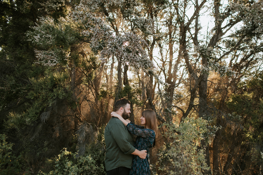 The sun is coming through the trees whilst a couple smile at each other embracing. Photography by Alpine Image Company