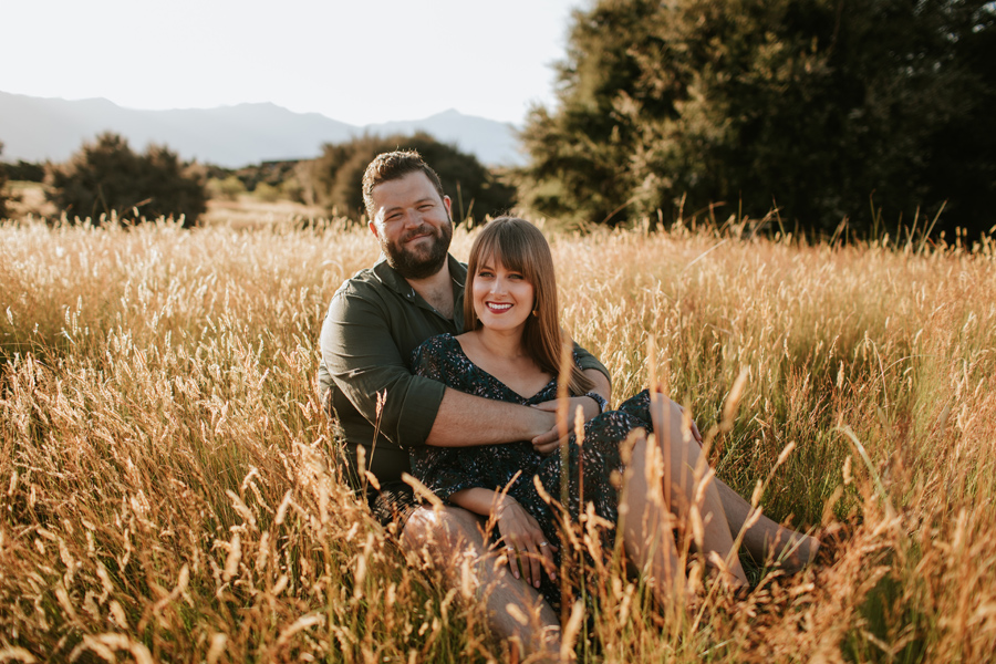 A couple sit in the golden grass smiling after their wedding day. Photography by Alpine Image Company