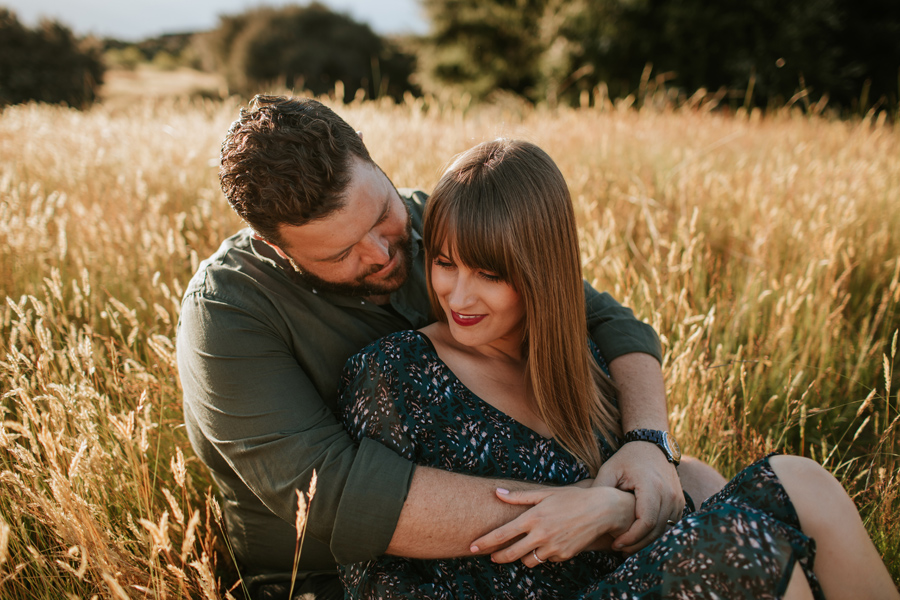 Close up photo of a couple on a post wedding shoot snuggling in a field of long grass in Wanaka, New Zealand. Photography by Alpine Image Company.