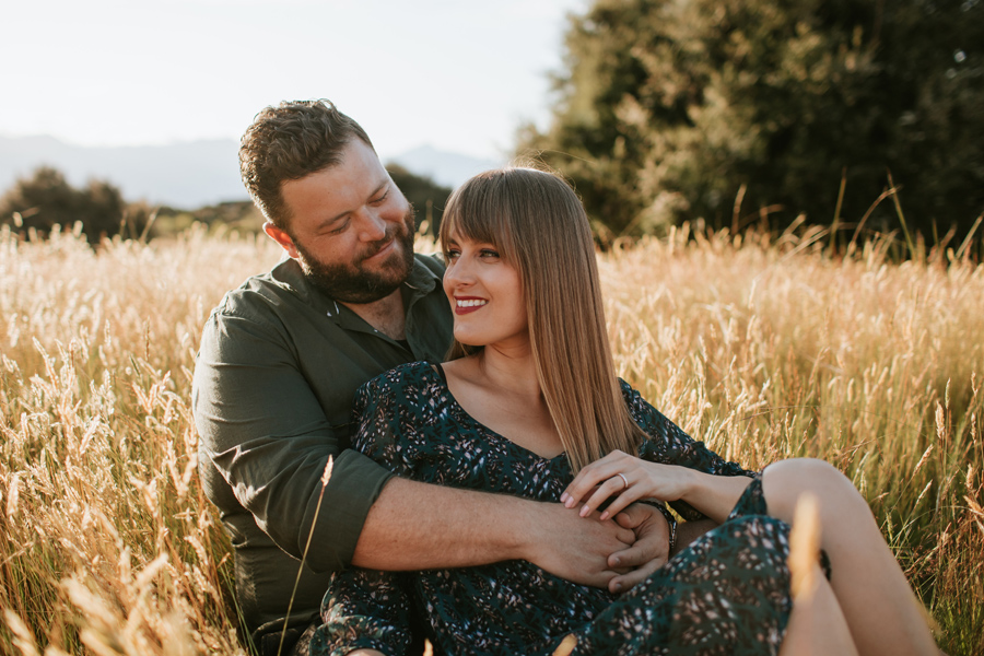 Surrounded by a field of long golden grass a happy couple sit smiling. Photography by Alpine Image Company.