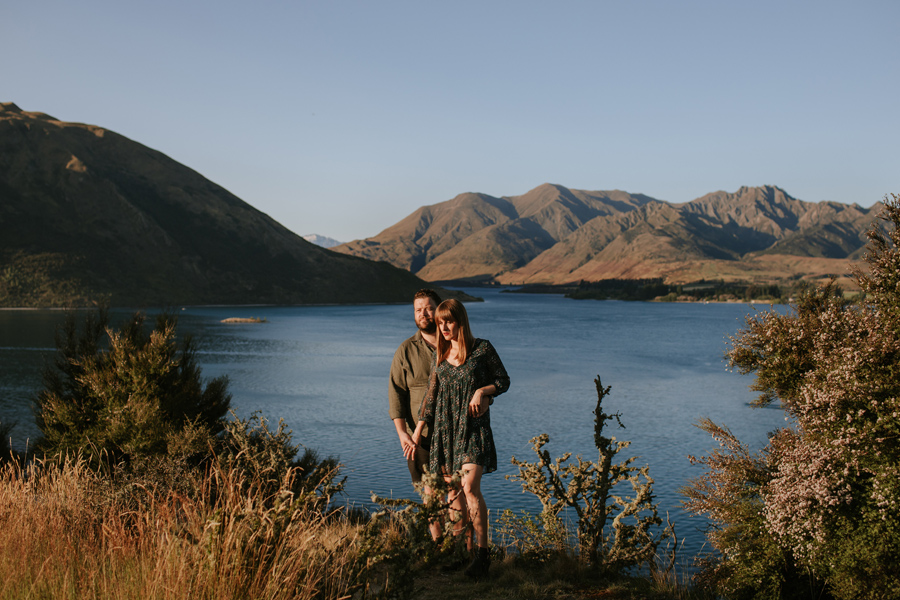 The beautiful last of the evening light kisses the couple who pose above lake Wanaka and Mt Gold in the background. Photography by Alpine Image Company.