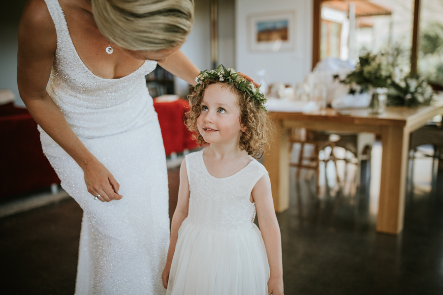 A flower girl looks lovingly at her aunty, who is the bride. With photography by Alpine Image Company