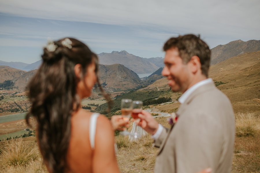 Bride and groom cheers their champagne flutes out of focus in the foreground whilst the focus is on cecil peak and the Queenstown lake in the distance. Photography by Alpine Image Company.