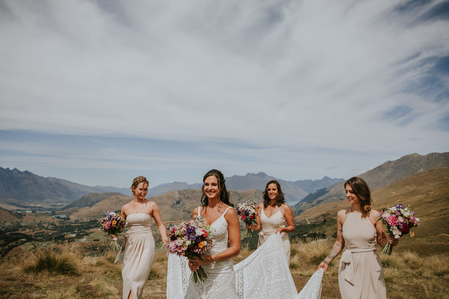 3 bridesmaids carry the brides train of her dress whilst also carrying their colourful bouquet of flowers up coronet peak. Photography by Alpine Image Company
