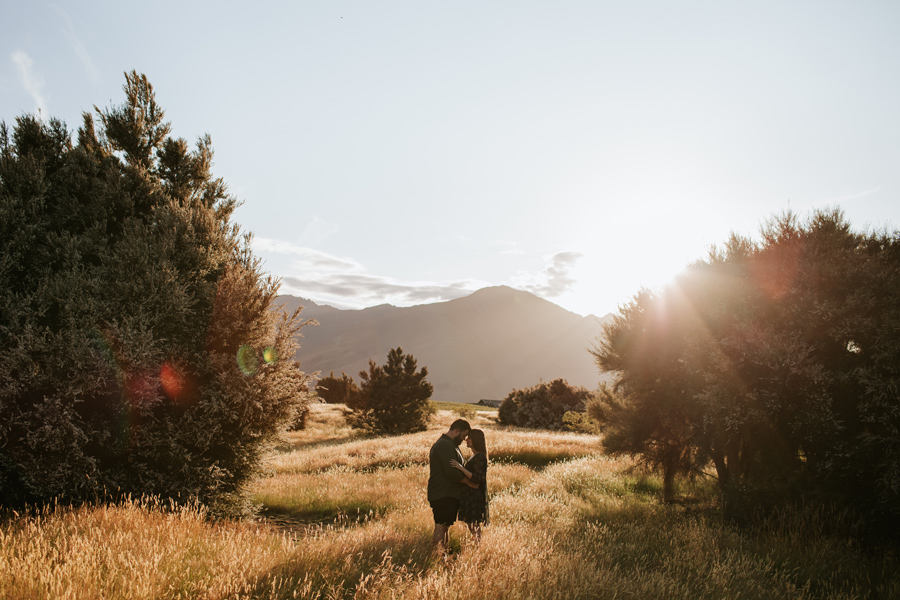 A couple touch foreheads with Mt Roy behind them and a sun flare coming through the trees. They are surrounded by long grass in the golden hour. Photography by Alpine Image Company