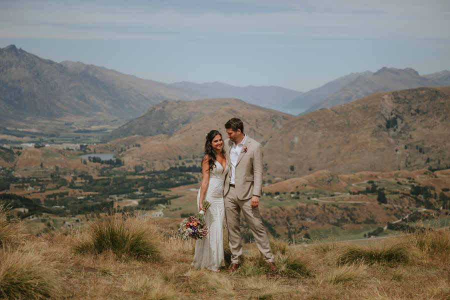 A bride and groom on their wedding day look at each other whilst cuddling up Coronet Peak in Queenstown. Photography by Alpine Image Company.