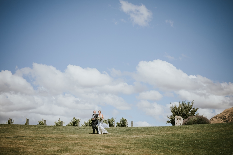 A bride walks down the aisle with her father, on her wanaka wedding day. With photography by Alpine Image Company