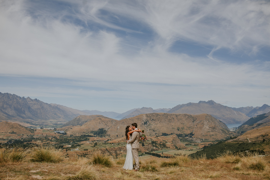 A bride and groom cuddle up close on a beautiful summers wedding day, with the mountains and lake in view behind them. Photography by Alpine Image Company.