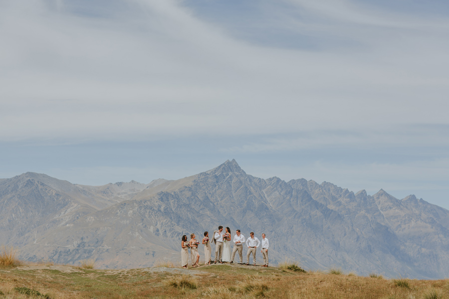 The remarkable mountains of Queenstown are in the background, the sky is blue and a bridal party of 8 stand centered and small in the frame.. Photography by Alpine Image Company.