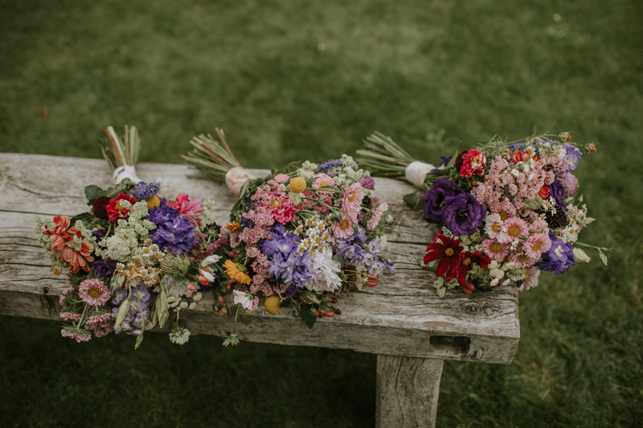 Close up photos of three colourful wildflower bridal bouquets on a wooden bench. Photography by Alpine Image Company.