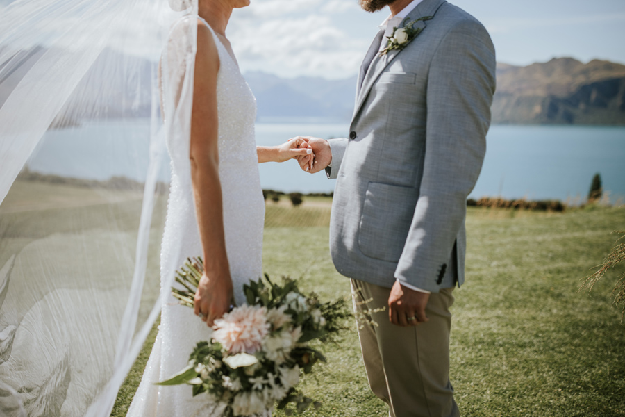 A bride and groom hold hands during their wedding ceremony. There are lakes and mountains in the distance. With photography by Alpine Image Company