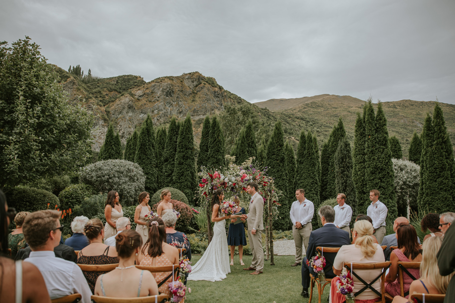 The ceremony set up at the Winehouse Vineyard and kitchen in Queenstown. the bride and groom along with their bridal party are lined up at the front. Photography by Alpine Image Company.