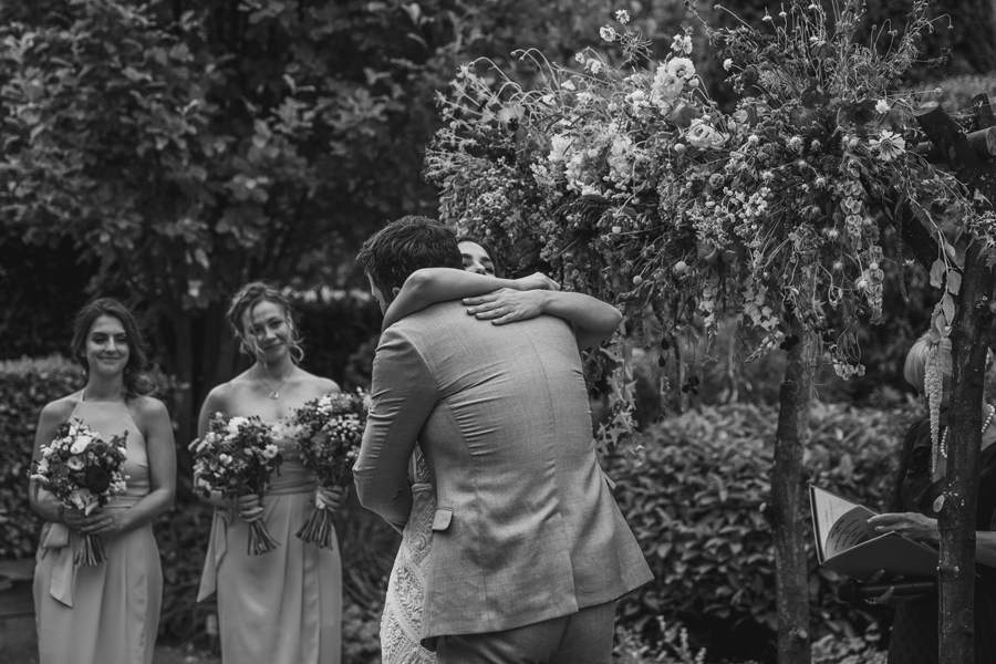 A black and white photo of a bride and groom hugging under the alter during their wedding ceremony in Queenstown. Photography by Alpine Image Company.