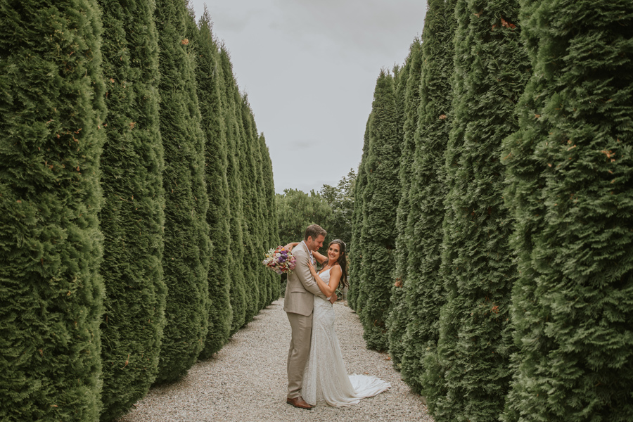 On a gravel path surrounded by high green hedges a bride and groom cuddle up central in the photo whilst smiling on their wedding day in Queenstown. Photography by Alpine Image Company.