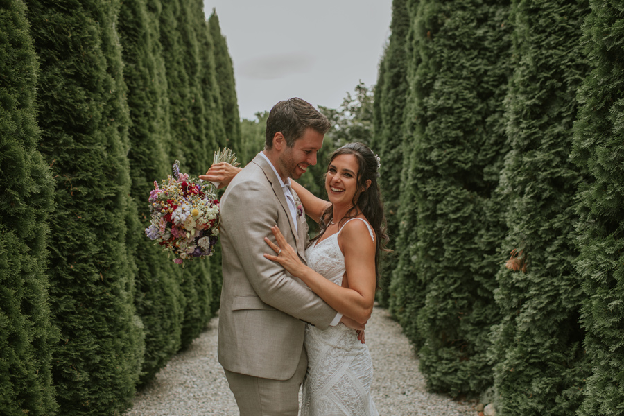 A bride and grrom smile happily whilst cuddled up on a gravel path between high green hedges at the winehouse venue in Queenstown. Photography by Alpine Image Company.