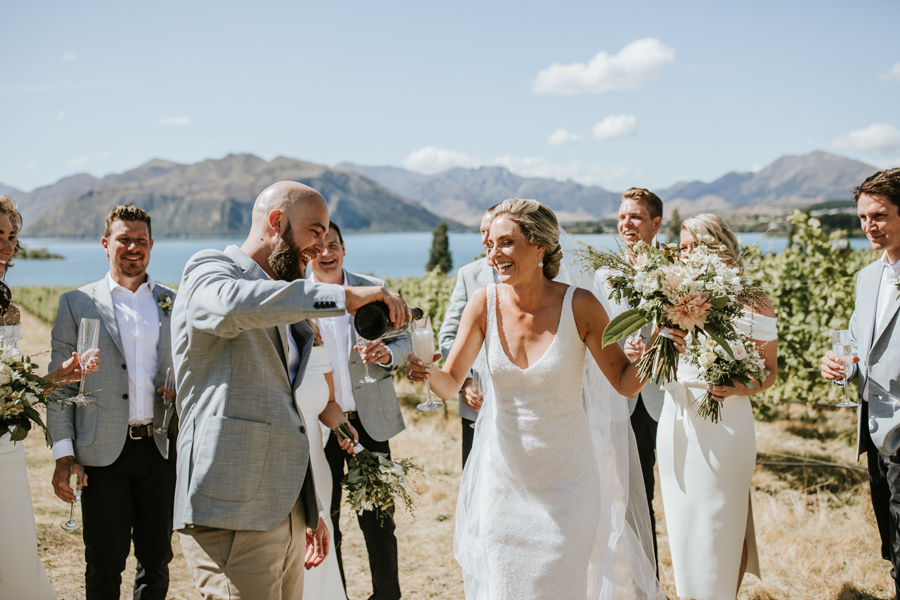 A groom pours a glass of champagne for his bride. The bridal party laughs in the background. They stand in front of mountains and a blue lake. With photography by Alpine Image Company
