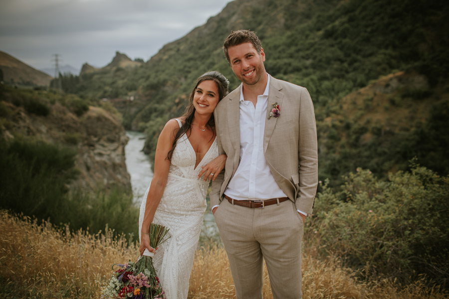 High above the Kawara River in Queenstown a bride and groom cuddle on their wedding day. The grass is long and golden and the bushes on the banks are green. Photography by Alpine Image Company.