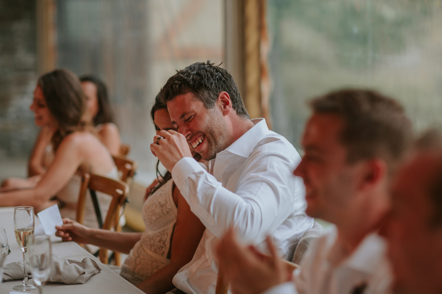 A groom laughs during a speech whilst seated for dinner during his wedding in Queenstown. Photography by Alpine Image Company.