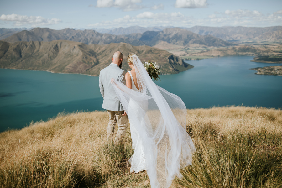 A bride and groom walk through fields of grass on a mountain, on their Wanaka Wedding day. With photography by Alpine Image Company