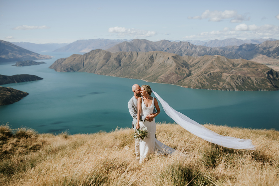A bride and groom embrace on a mountain top on their wanaka wedding day. There are mountains in the background and a blue lake. With photography by Alpine Image Company