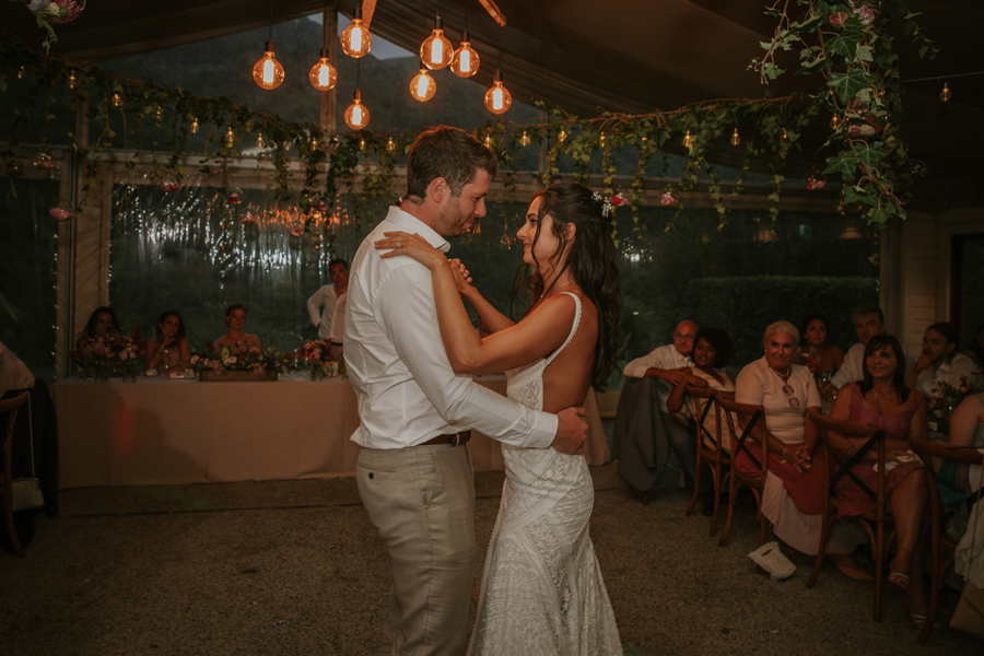A bride and groom dancing together for their first dance as husband and wife on their wedding day. There are festoon lights all around and the guests behind are watching them.. Photography by Alpine Image Company.