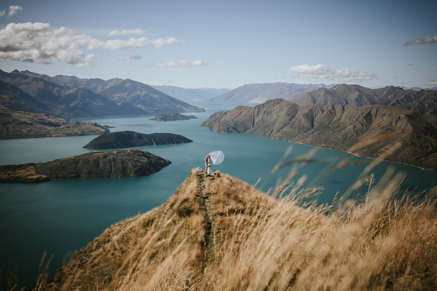 A bride and groom embrace on the peak of Coromandel Peak, on their Wanaka wedding day. The sky is blue and there are mountains in the background. With photography by Alpine Image Company