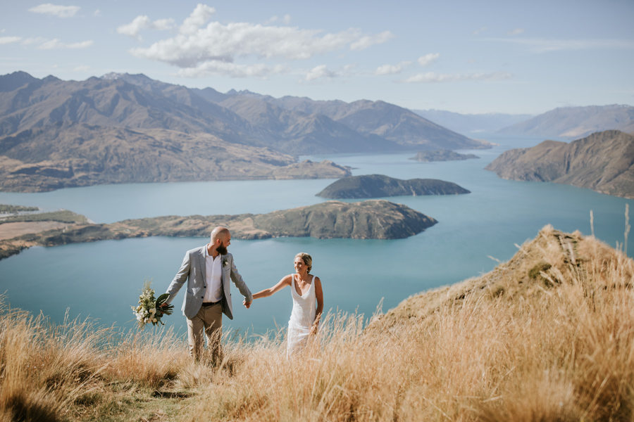 A bride and groom walk through long dry grass on Coromandel Peak on their Wanaka Wedding Day. There is a lake and mountains in the background, and the sky is blue. With photography by Alpine Image Company