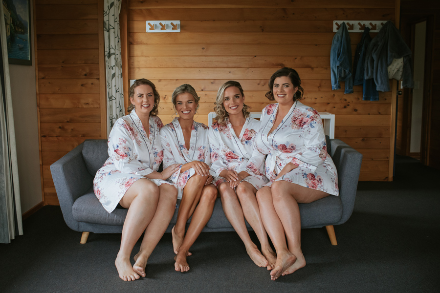 Bride and Bridesmaids sit in their robes on a sofa smiling on the morning of their Wanaka Wedding. Photography by Alpine Image Company.