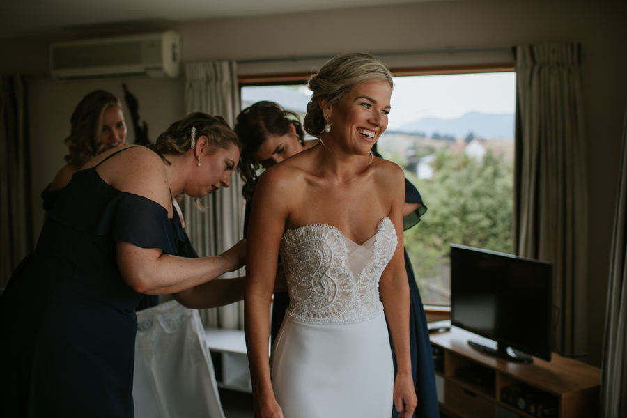 A bride is being dressed by her bridesmaids on the morning of her Wanaka wedding. Photography by Alpine Image Company