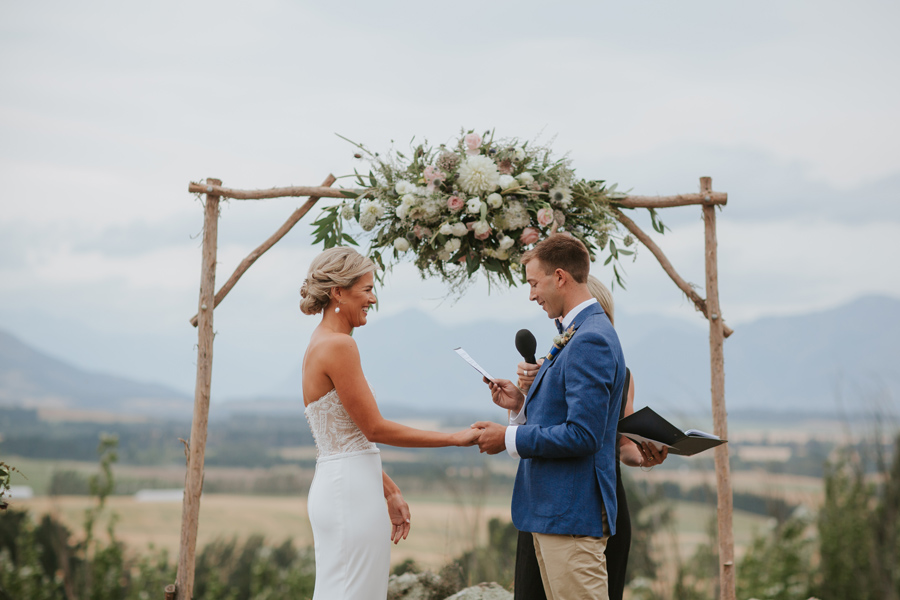 A groom in a blue suit jacket reads his vows and holds hands with his wife to be on his Wanaka wedding day. Photography by Alpine Image Company.