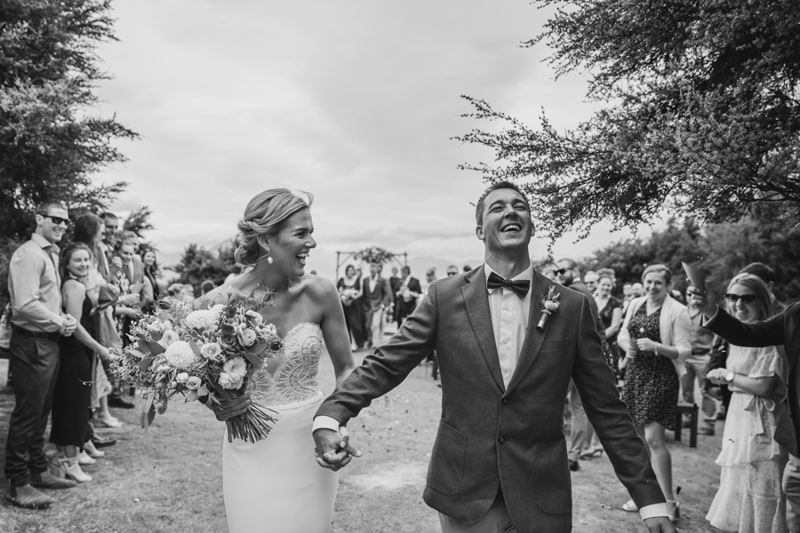 A black and white photo of a very happy couple exiting their wedding ceremony in wanaka. Photography by Alpine Image Company.